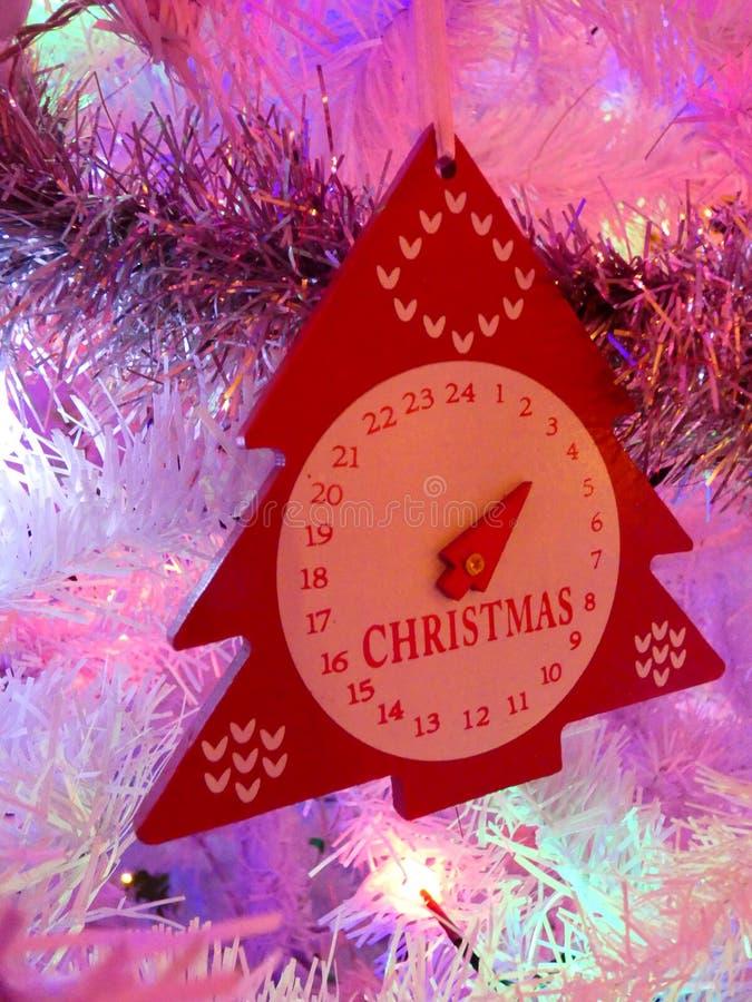 Κόκκινη διακόσμηση Χριστουγέννων ενός δέντρου με ένα ρολόι που κρεμά σε έναν κλάδο σε ένα άσπρο χριστουγεννιάτικο δέντρο στοκ εικόνα
