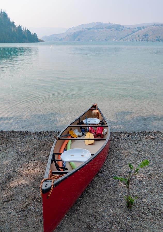 Κόκκινη ελαφριά βάρκα κανό σε μια ακτή της λίμνης Kalamalka στοκ φωτογραφία με δικαίωμα ελεύθερης χρήσης
