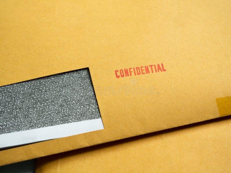 Κόκκινη εμπιστευτική ` λέξη ` που τυπώνεται στον καφετή εκλεκτής ποιότητας φάκελο Επιχειρησιακό εμπιστευτικό concep στοκ εικόνα