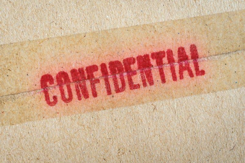 Κόκκινη εμπιστευτική ` λέξη ` που τυπώνεται στον καφετή εκλεκτής ποιότητας φάκελο στοκ εικόνες με δικαίωμα ελεύθερης χρήσης