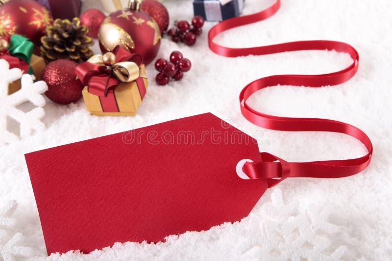 Κόκκινη ετικέττα δώρων Χριστουγέννων που βάζει στο υπόβαθρο χιονιού με τα διάφορες δώρα και τις διακοσμήσεις στοκ φωτογραφία
