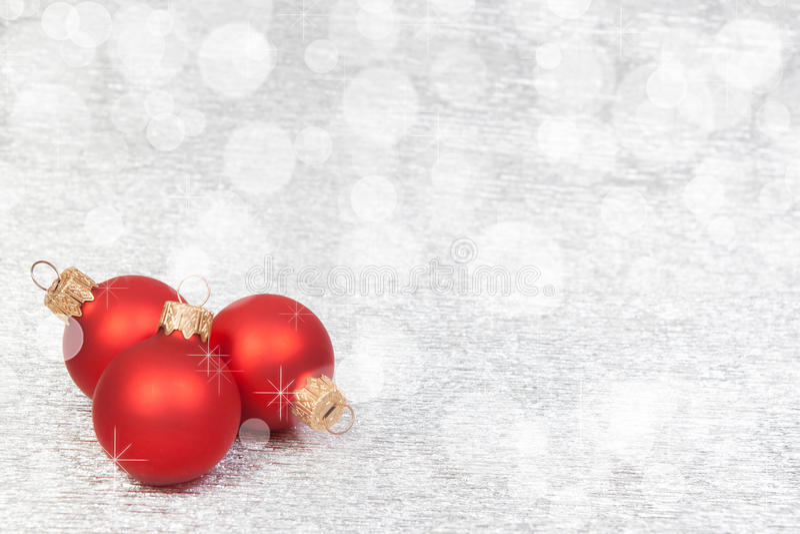 Κόκκινη διακόσμηση Χριστουγέννων σε ένα υπόβαθρο bokeh με το copyspace στοκ εικόνα