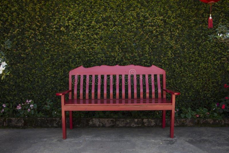 Κόκκινη καρέκλα μπροστά από τον τοίχο φύλλων στοκ φωτογραφία με δικαίωμα ελεύθερης χρήσης