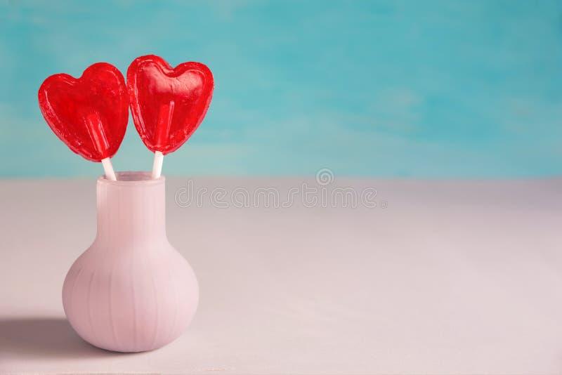Κόκκινη καραμέλα Lollipops μορφής καρδιών δύο στα ραβδιά στη μίμηση βάζων των λουλουδιών Τυρκουάζ υπόβαθρο Ρομαντική αγάπη βαλεντ στοκ εικόνα με δικαίωμα ελεύθερης χρήσης