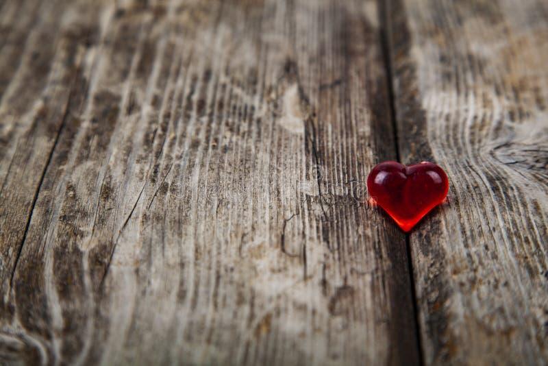Κόκκινη καρδιά γυαλιού σε ένα ξύλινο υπόβαθρο στοκ φωτογραφίες με δικαίωμα ελεύθερης χρήσης