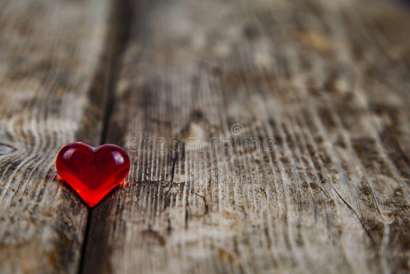 Κόκκινη καρδιά γυαλιού σε ένα παλαιό ξύλινο υπόβαθρο στοκ εικόνες