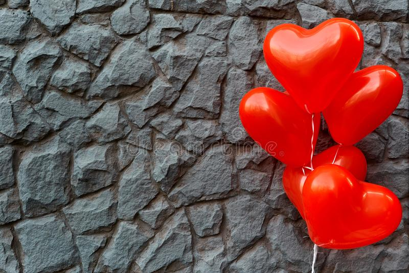 Κόκκινη καρδιά μπαλονιών σε ένα υπόβαθρο της γκρίζας πέτρας στοκ φωτογραφία