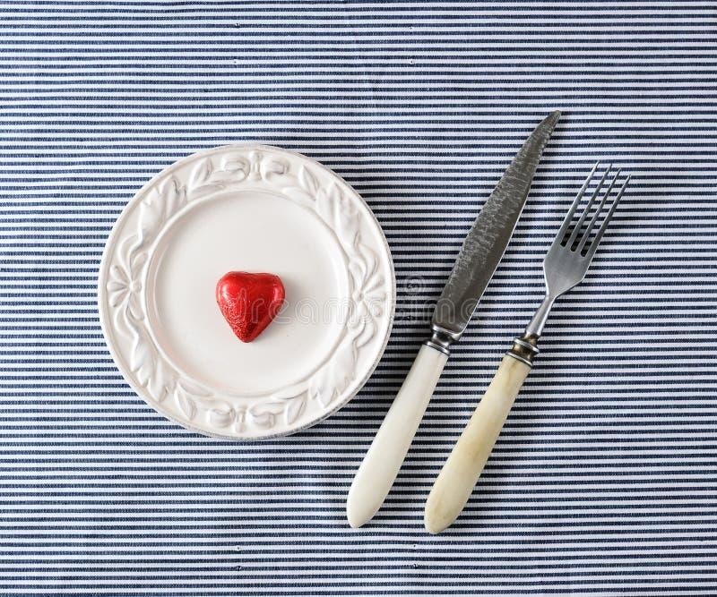 Κόκκινη καρδιά σοκολάτας στα πιάτα και μαχαίρι με ένα δίκρανο στοκ φωτογραφία με δικαίωμα ελεύθερης χρήσης