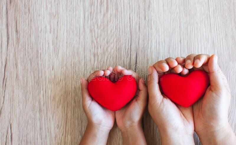 Κόκκινη καρδιά στα χέρια παιδιών και τα χέρια γονέων στο ξύλινο επιτραπέζιο υπόβαθρο στοκ εικόνες με δικαίωμα ελεύθερης χρήσης