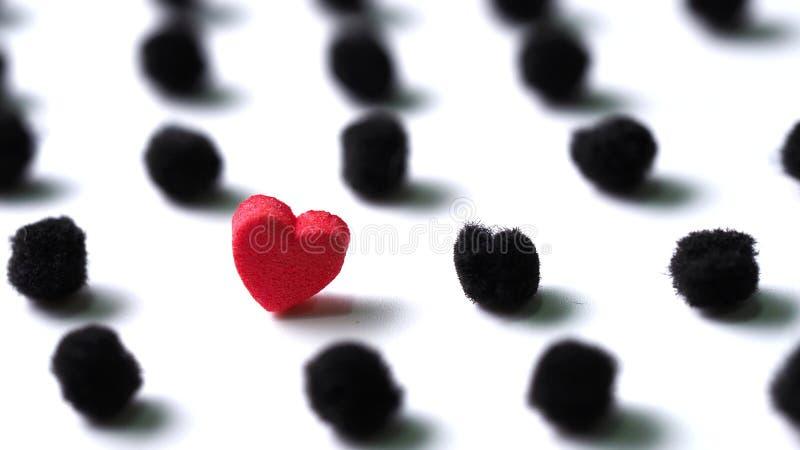 Κόκκινη καρδιά στο μαύρο σημείο Πόλκα pom poms στο άσπρο υπόβαθρο στοκ φωτογραφία