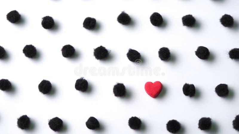 Κόκκινη καρδιά στο μαύρο σημείο Πόλκα pom poms στο άσπρο υπόβαθρο στοκ εικόνες