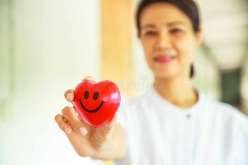 Κόκκινη καρδιά χαμόγελου που κρατιέται με το χαμόγελο του θηλυκού χεριού νοσοκόμων ` s, που αντιπροσωπεύει δίνοντας την προσπάθει στοκ εικόνες