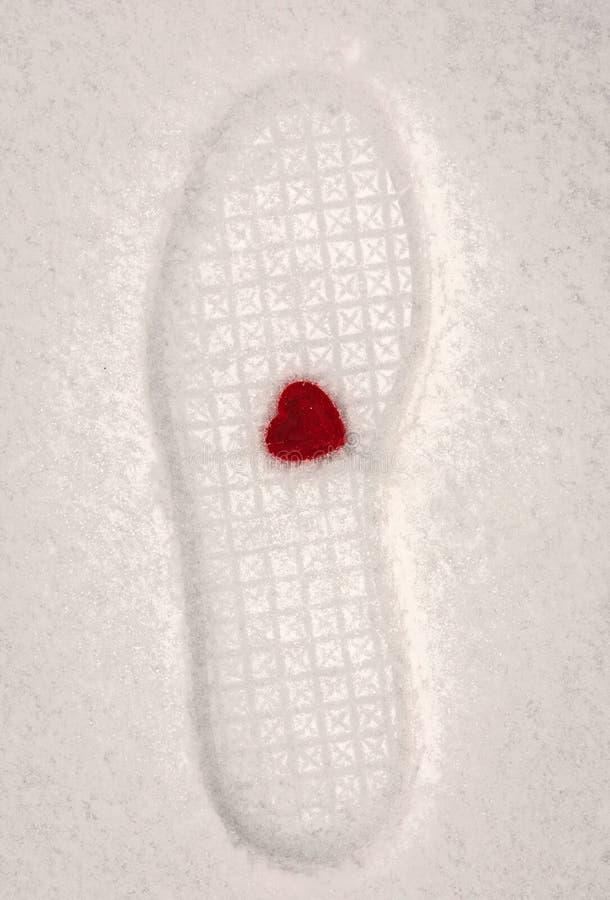 Κόκκινη καρδιά βελούδου με πολύ ποδοπατημένος στο χιόνι στοκ εικόνες