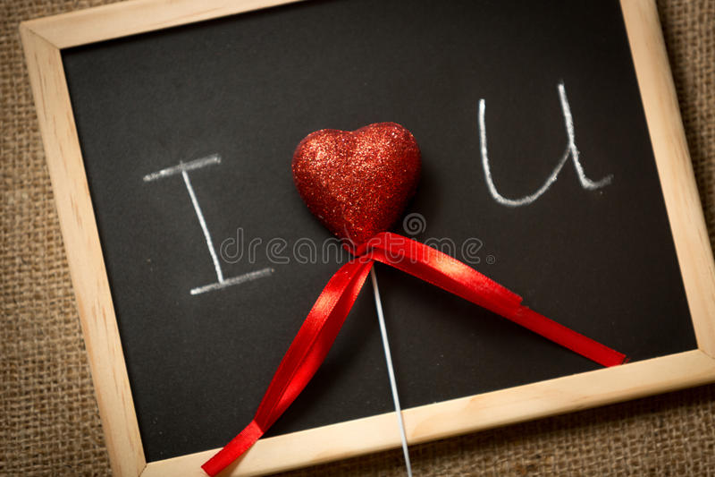 Κόκκινη καρδιά που βρίσκεται στον πίνακα με τη γραπτή δήλωση της αγάπης στοκ εικόνες