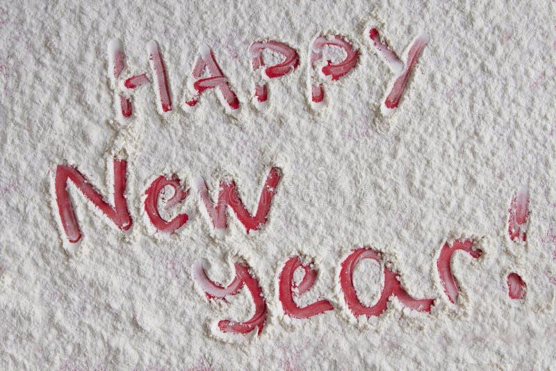 Κόκκινη καλή χρονιά που γράφεται στο άσπρο υπόβαθρο αλευριού στοκ εικόνα με δικαίωμα ελεύθερης χρήσης