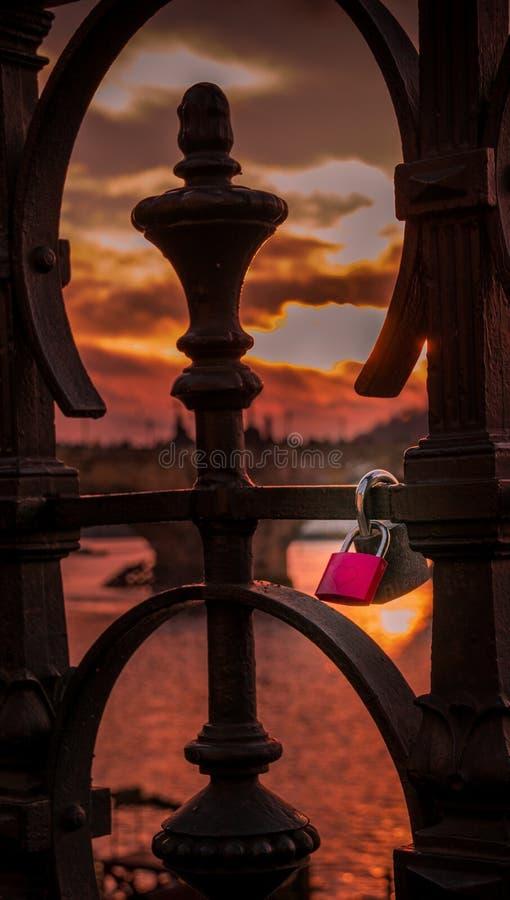 Κόκκινη κλειδαριά που κλειδώνεται στη ράγα μιας γέφυρας στοκ εικόνες