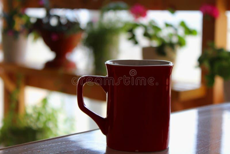 Κόκκινη κούπα σε ένα υπόβαθρο των λουλουδιών στοκ εικόνες