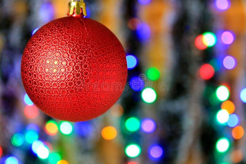 Κόκκινη κρεμώντας σφαίρα, διακόσμηση Χριστουγέννων με το θολωμένο υπόβαθρο φω'των στοκ εικόνα με δικαίωμα ελεύθερης χρήσης