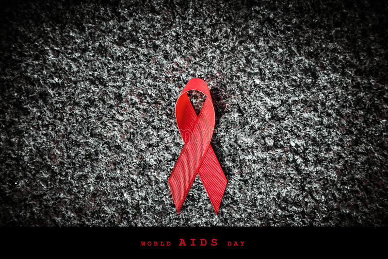 Κόκκινη κόκκινη κορδέλλα κορδελλών σε μια πέτρα, έννοια Παγκόσμιας Ημέρας κατά του AIDS στοκ εικόνες