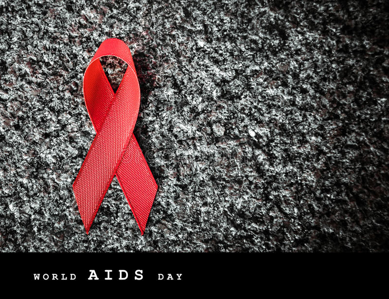 Κόκκινη κόκκινη κορδέλλα κορδελλών σε μια πέτρα, έννοια Παγκόσμιας Ημέρας κατά του AIDS στοκ φωτογραφίες
