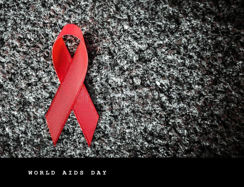 Κόκκινη κόκκινη κορδέλλα κορδελλών σε μια πέτρα, έννοια Παγκόσμιας Ημέρας κατά του AIDS στοκ φωτογραφία με δικαίωμα ελεύθερης χρήσης