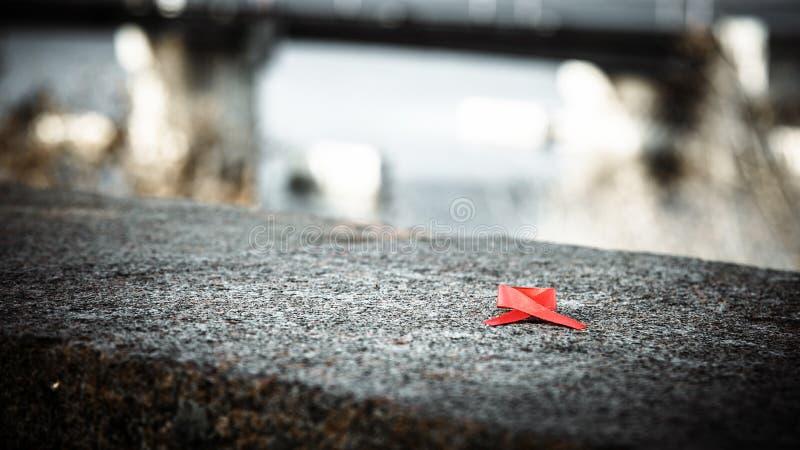 Κόκκινη κόκκινη κορδέλλα κορδελλών σε μια πέτρα, έννοια Παγκόσμιας Ημέρας κατά του AIDS στοκ εικόνες με δικαίωμα ελεύθερης χρήσης