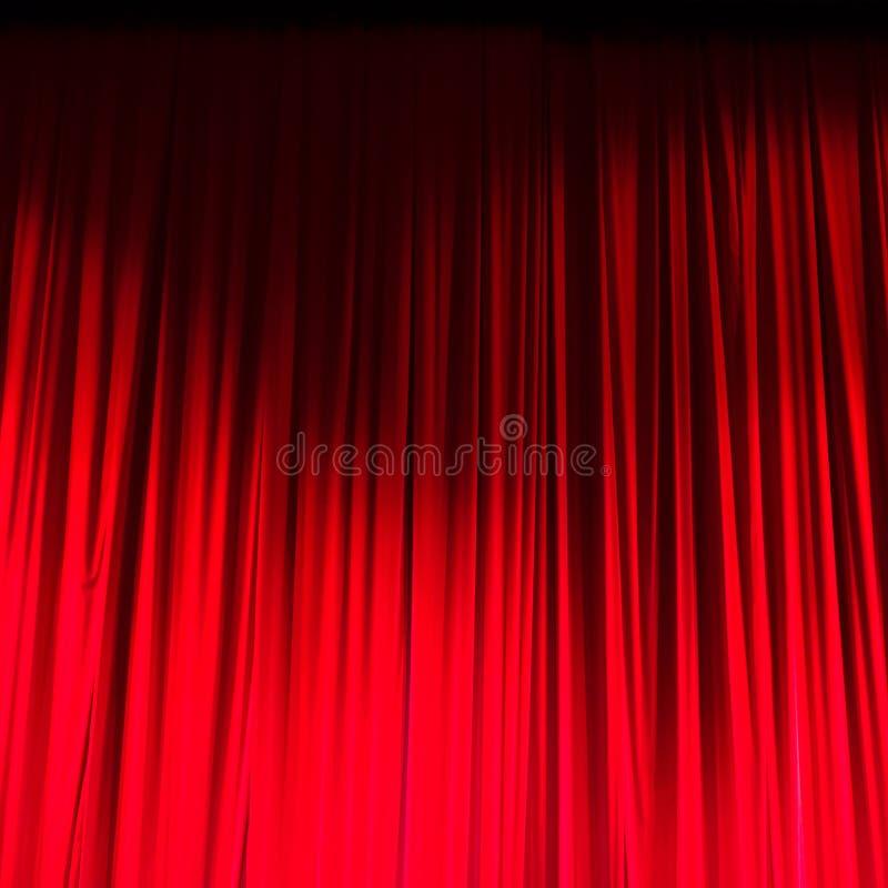 Κόκκινη κλειστή κουρτίνα με τα ελαφριά σημεία σε ένα θέατρο στοκ φωτογραφίες
