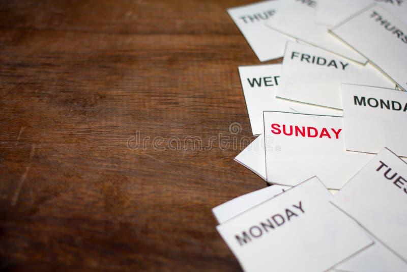 Κόκκινη λέξη της Κυριακής με μια άλλη ημέρα στο ξύλινο υπόβαθρο στοκ εικόνες
