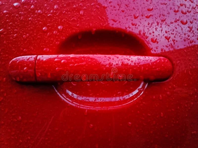 Κόκκινη λαβή αυτοκινήτων που καλύπτεται με τις πτώσεις βροχής στοκ φωτογραφίες με δικαίωμα ελεύθερης χρήσης