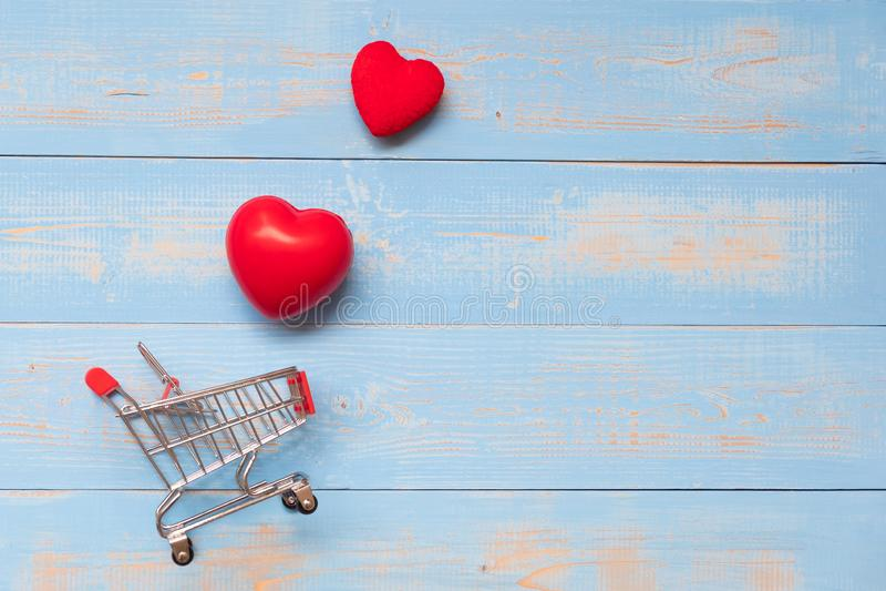 κόκκινη μορφή καρδιών ζευγών με το μίνι κάρρο αγορών στον μπλε ξύλινο πίνακα κρητιδογραφιών αγάπη, αγορές και έννοια ημέρας βαλεν στοκ εικόνα