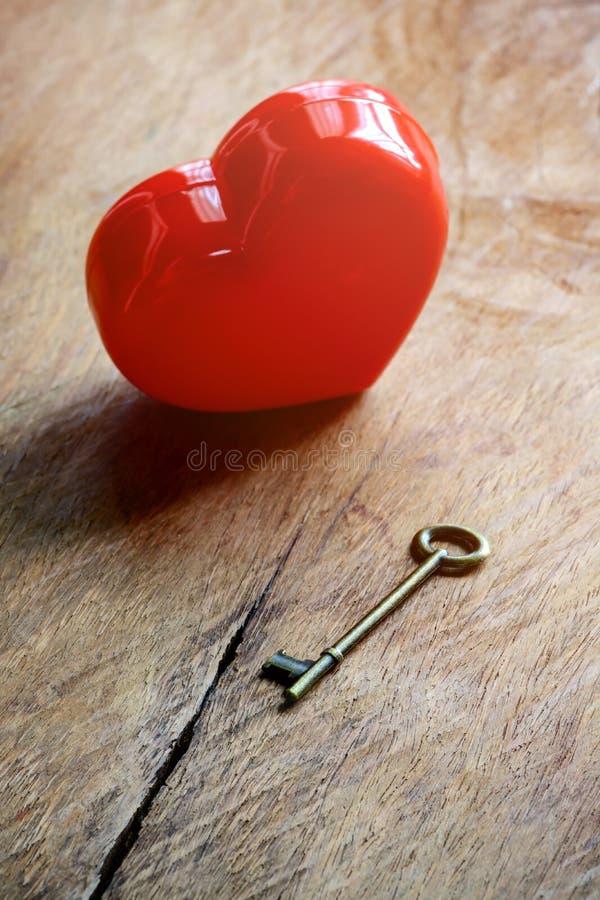 Κόκκινη μορφή καρδιών με το κλειδί παλαιό σε ξύλινο στοκ εικόνα με δικαίωμα ελεύθερης χρήσης