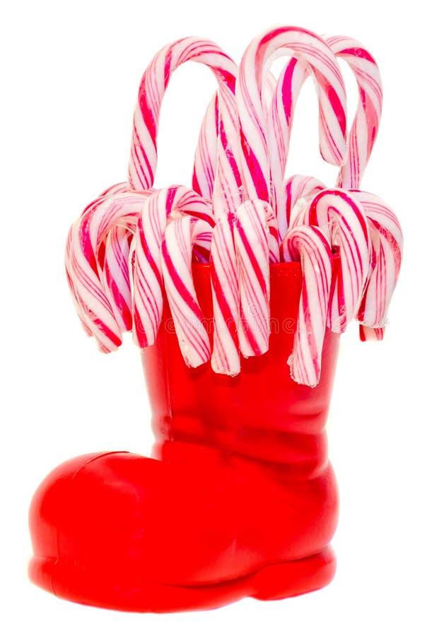 Κόκκινη μπότα Άγιου Βασίλη, παπούτσι με τα χρωματισμένα γλυκά lollipops, candys Η μπότα Άγιου Βασίλη με παρουσιάζει τα δώρα στοκ φωτογραφίες