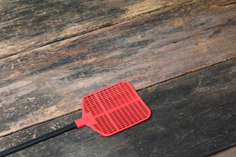 Κόκκινη μύγα swatter, αντικείμενο φιαγμένο από πλαστικό στο ξύλινο υπόβαθρο πατωμάτων στοκ φωτογραφίες με δικαίωμα ελεύθερης χρήσης