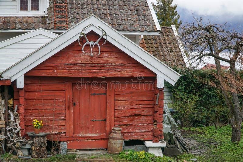 Κόκκινη ξύλινη καμπίνα κατά μήκος του φιορδ στη Νορβηγία στοκ φωτογραφία