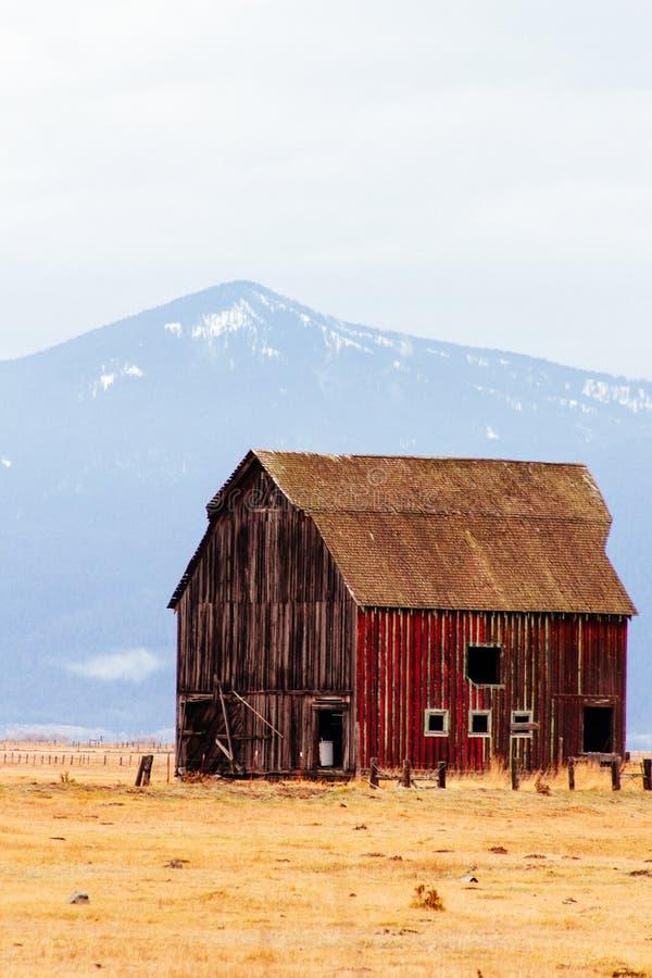 Κόκκινη ξύλινη σιταποθήκη σε έναν μεγάλο τομέα με τα βουνά και λόφοι στο υπόβαθρο στοκ εικόνες