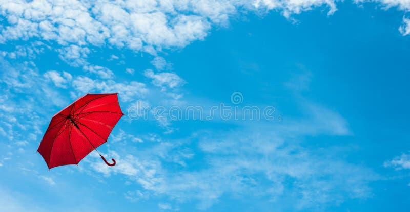 Κόκκινη ομπρέλα με το μπλε ουρανό στοκ εικόνες