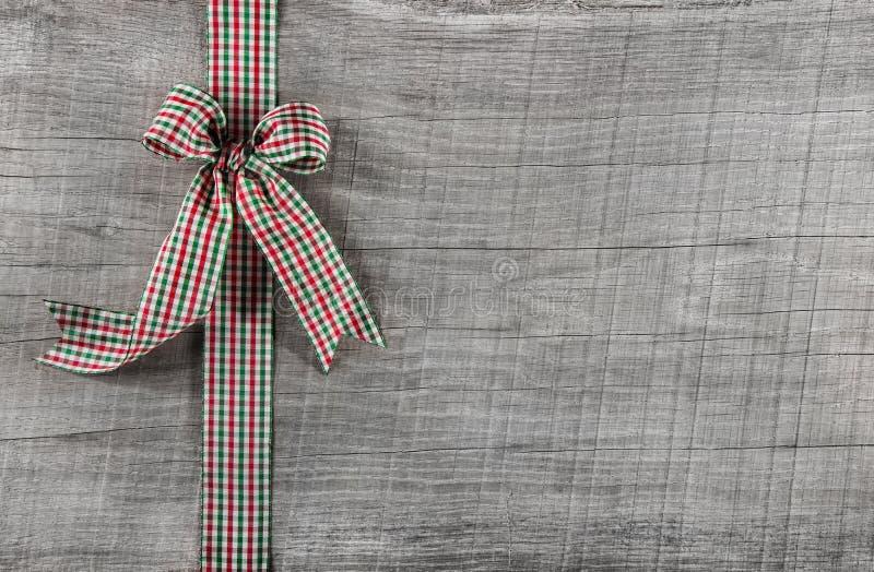 Κόκκινη πράσινη ελεγχμένη κορδέλλα στο ξύλινο υπόβαθρο για τα Χριστούγεννα ή το ο στοκ εικόνες