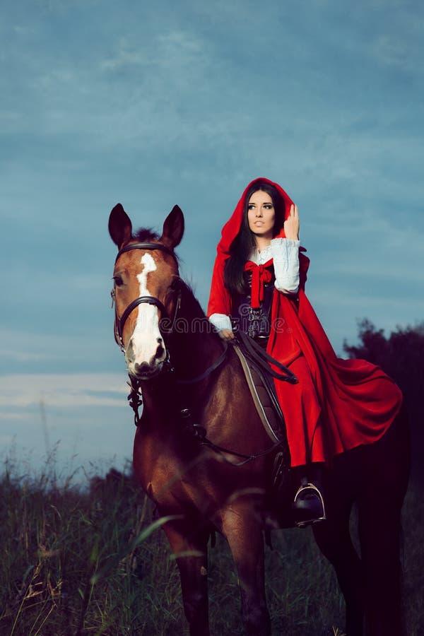 Κόκκινη πριγκήπισσα κουκουλών που οδηγά ένα άλογο στοκ φωτογραφίες