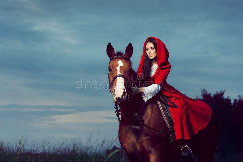 Κόκκινη πριγκήπισσα κουκουλών που οδηγά ένα άλογο στοκ εικόνες