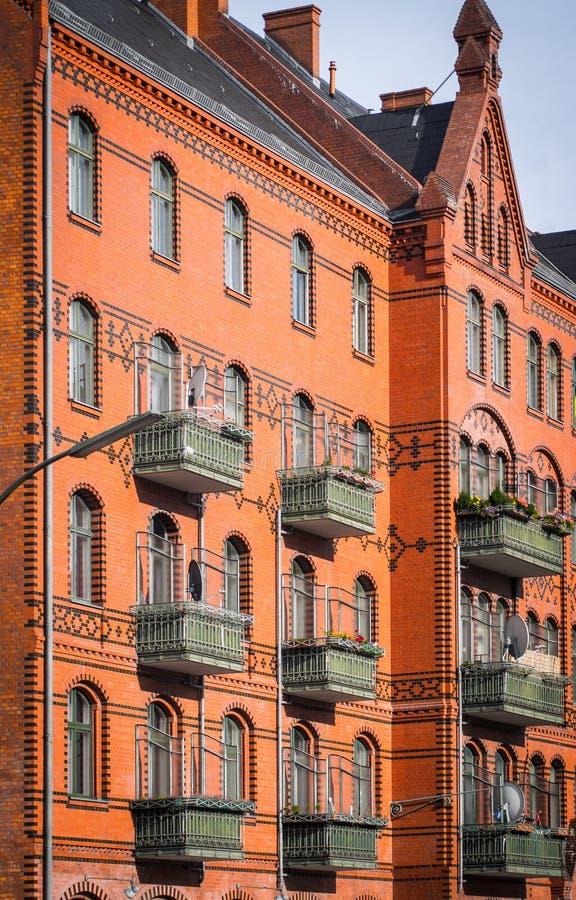 Κόκκινη πρόσοψη του τουβλότοιχος του κτηρίου ευρωπαϊκός-ύφους με τα παράθυρα και τα πράσινα μπαλκόνια στοκ εικόνες με δικαίωμα ελεύθερης χρήσης