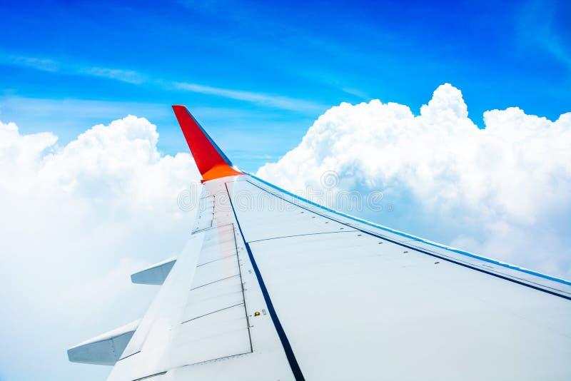 Κόκκινη πτέρυγα της προβολής του αεροσκάφους από το κάθισμα του παραθύρου του αεροπλάνου που πετάει στον γαλάζιο ουρανό με φόντο  στοκ φωτογραφίες