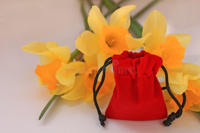 Κόκκινη σακούλα βελούδου με τα κίτρινα λουλούδια σε ένα άσπρο υπόβαθρο που απομονώνεται στοκ εικόνες με δικαίωμα ελεύθερης χρήσης