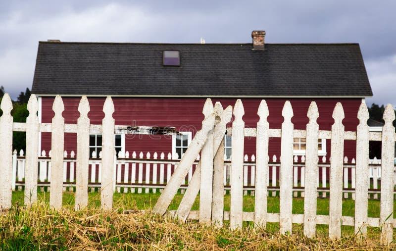 Κόκκινη σιταποθήκη με τον άσπρο φράκτη στύλων στοκ φωτογραφία