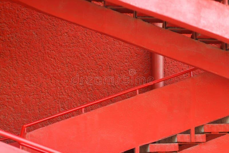 Κόκκινη σκάλα κοντά στον κόκκινο τοίχο στοκ εικόνες
