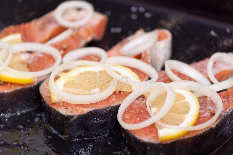 Κόκκινη σολομός ή πέστροφα μπριζολών ψαριών με το λεμόνι, χορτάρια στο μαύρο υπόβαθρο στοκ φωτογραφίες με δικαίωμα ελεύθερης χρήσης