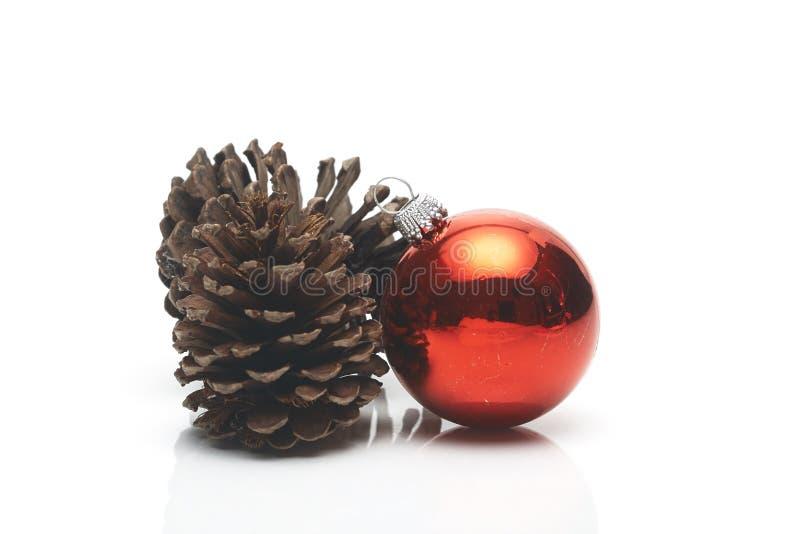 Κόκκινη σφαίρα διακοσμήσεων Χριστουγέννων κώνων πεύκων στοκ φωτογραφία