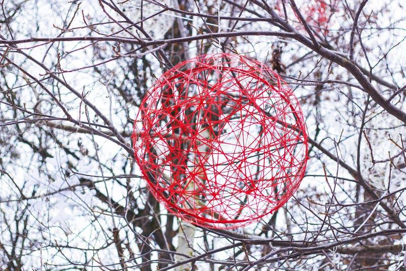 Κόκκινη σφαίρα διακοσμήσεων Χριστουγέννων της ένωσης νημάτων στο δέντρο στοκ φωτογραφία με δικαίωμα ελεύθερης χρήσης