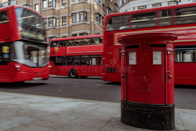 Κόκκινη ταχυδρομική θυρίδα στο Λονδίνο με το διπλό λεωφορείο καταστρωμάτων που περνά από στοκ φωτογραφίες