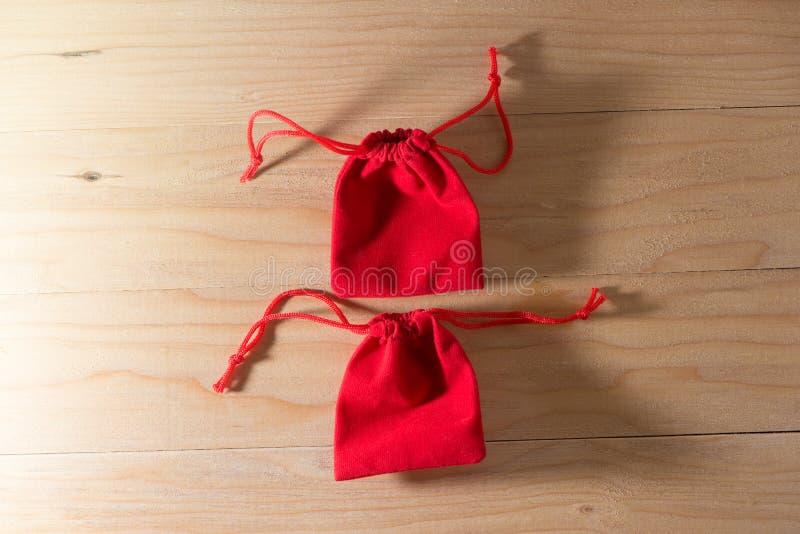 Κόκκινη τσάντα δώρων στα παλαιά Shabby ξύλινα Χριστούγεννα και Newyear επιτραπέζιας έννοιας στοκ εικόνα με δικαίωμα ελεύθερης χρήσης