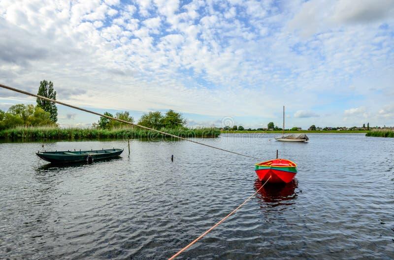 Κόκκινη χρωματισμένη βάρκα κωπηλασίας που δένεται σε έναν πόλο σιδήρου στο νερό στοκ εικόνα
